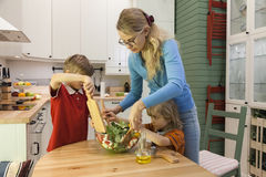 Kids helping mother preparing vegetable salad. Mother preparing vegetable salad. Children helping on the kitchen Royalty Free Stock Photography