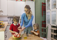 Kids helping mother preparing vegetable salad. Family preparing healthy food in the kitchen Stock Images