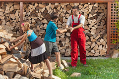 Kids helping their father to stack the firewood Stock Photography
