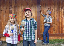 Kids helping their mother painting the wood shed Royalty Free Stock Photos