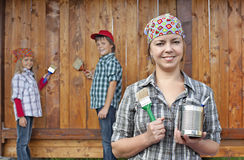 Kids helping their mother painting the wood shed Stock Photos
