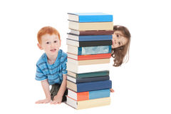 Kids hiding behind school books. Two kids hiding behind stack of books. Isolated on white Stock Image