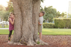 Kids hiding behind a tree. Boy and girl hiding from behind a tree Royalty Free Stock Photography