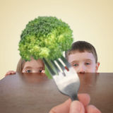 Kids Hiding from Healthy Broccoli Food. Two little kids are hiding behind a table from a fork with a healthy piece of broccoli on it for a childhood nutrition or Stock Images
