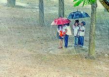 Kids hiding under umbrella Royalty Free Stock Images