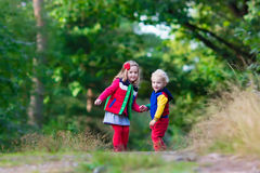 Kids hiking in autumn park. Kids playing in autumn park. Children play outdoors on a sunny fall day. Boy and girl running together hand in hand in a forest Royalty Free Stock Photos