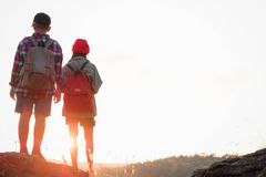 Kids hiking with backpacks, Relax time on holiday concept travel. Silhouette two kids hiking with backpacks walking studying the route map in a sunny summer day royalty free stock image