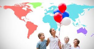 Kids holding balloons in front of colorful world map. Digital composite of Kids holding balloons in front of colorful world map stock image