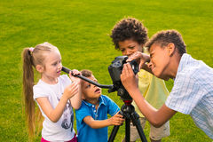 Kids are holding a camera. Stock Photo