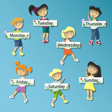 Kids holding cards saying days of the week Royalty Free Stock Image