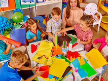 Kids holding colored paper and glue on table in Stock Photography