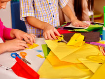 Kids holding colored paper on table in Stock Photography