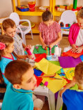 Kids holding colored paper on table in Stock Photo