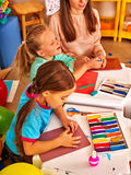 Kids holding colored paper on table in Stock Images