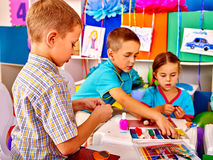 Kids holding colored paper on table in Royalty Free Stock Photos