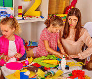 Kids holding colored paper on table in kindergarten . Royalty Free Stock Image