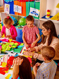Kids holding colored paper on table in kindergarten . Stock Photography