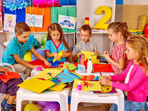 Kids holding colored paper on table in kindergarten . Stock Photo