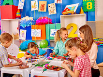 Kids holding colored paper on table in Royalty Free Stock Photography