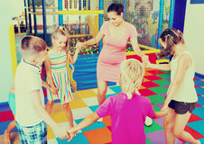 Kids holding each others hands and dancing with teacher Stock Photo