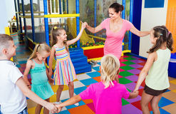 Kids holding each others hands and dancing with teacher Royalty Free Stock Photography