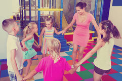 Kids holding each others hands and dancing with teacher. Positive laughing kids holding each others hands and dancing with teacher at school class Royalty Free Stock Photo