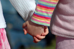 Kids holding hands. Two white little hands of caucasian children who are best friends holding each other while standing together on the playground outdoors Stock Photo