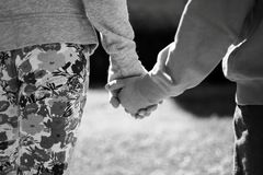 Kids holding hands. Young girl and boy holding hands together and walking outdoors Royalty Free Stock Images