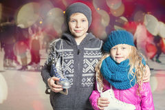Kids holding ice skates shoes. At ice rink outdoor, sport and healthy lifestyle ice skating at Medeo stadium, Almaty, night. Cute children, boy and girl looking royalty free stock photo