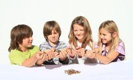 Kids holding money. Four happy kids - two girls and two boys holding money in hands - savings of czech crowns - small change Stock Photography