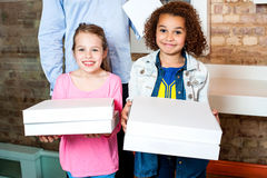 Kids holding pizza boxes Stock Image
