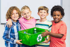 Kids holding recycled bottle in box Stock Photography