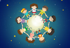 Kids holding their hands together while standing above the Earth Stock Images