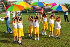 Kids holding umbrella at Kindergarten sport day. KUALA LUMPUR - 15 AUGUST 2010 : Unidentified children using umbrella to perform a dance at Taman Midah stock images
