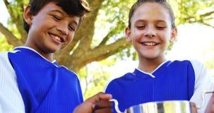 Kids holding winner trophy in park. Smiling kids holding winner trophy in park on a sunny day 4k stock video