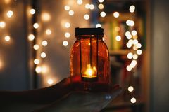 Kids holds Christmas lantern in hands on lights bokeh background. New year celebration concept, royalty free stock photo