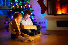 Kids at home on Christmas eve opening gifts Royalty Free Stock Photos