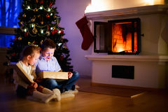 Kids at home on Christmas eve opening gifts Royalty Free Stock Images