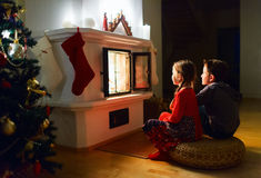 Kids at home on Christmas eve. Two little kids sitting by a fireplace at home on Christmas eve Royalty Free Stock Image