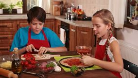 Kids at home making pizza spreading and tasting the sauce stock video
