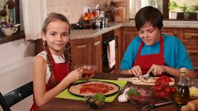Kids at home making a pizza spreading and tasting the sauce stock video footage
