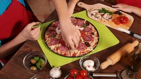 Kids at home making a pizza - top view. Kids at home making a pizza putting on the various topping ingredients - top view, closeup on hands stock footage
