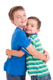 Kids hugging. A studio portrait of two young boys hugging.  White background Royalty Free Stock Photo