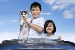 Kids and husky puppy on the sunroof Royalty Free Stock Photos