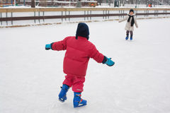 Kids ice skating. Two little kids enjoying ice skating outdoors Stock Photos