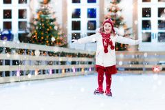 Kids ice skating in winter. Ice skates for child. Kids ice skating in winter park rink. Children ice skate on Christmas fair. Little girl with skates on cold royalty free stock images