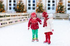 Kids ice skating in winter. Ice skates for child. Kids ice skating in winter park rink. Children ice skate on Christmas fair. Little girl and boy with skates on Stock Images