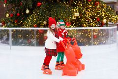 Kids ice skating in winter. Ice skates for child. Kids ice skating in winter park rink. Children ice skate on Christmas fair. Little girl and boy with skates on royalty free stock photography