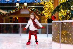 Kids ice skating in winter. Ice skates for child. Kids ice skating in winter park rink. Children ice skate on Christmas fair. Little girl with skates on cold stock images