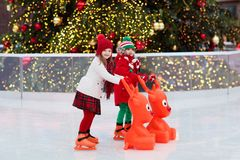 Kids ice skating in winter. Ice skates for child. Kids ice skating in winter park rink. Children ice skate on Christmas fair. Little girl and boy with skates on royalty free stock photos